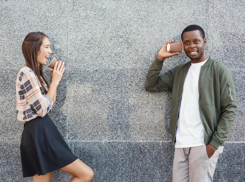 Multiracial couple talking through tin can phone stock images
