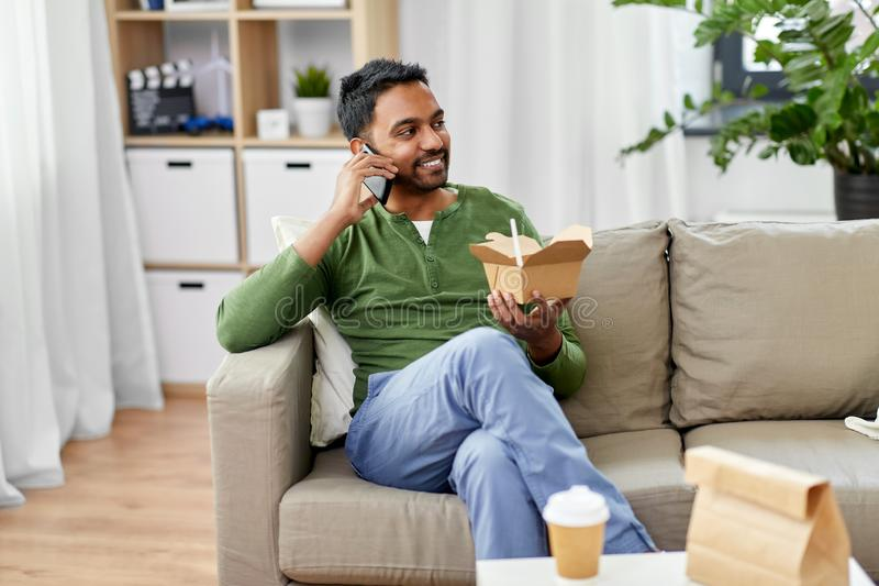 Smiling indian man eating takeaway food at home. Communication, leisure and people concept - smiling indian man calling on smartphone and eating takeaway food at royalty free stock photography