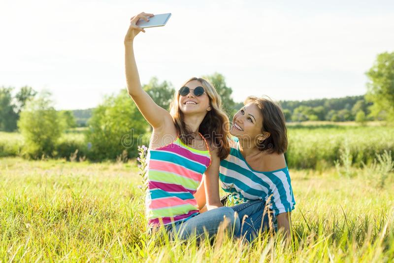 Communication between the mother and the teen daughter. Photos on a smartphone together. royalty free stock images