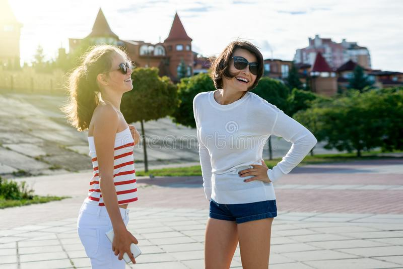 Mom and daughter teenager talking and laughing stock photography