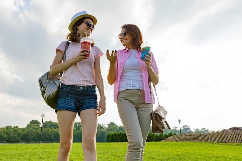 Communication of parent and teenager. Mother is talking to her teen daughter for 14 years, walking around the park on sunny summer royalty free stock photo