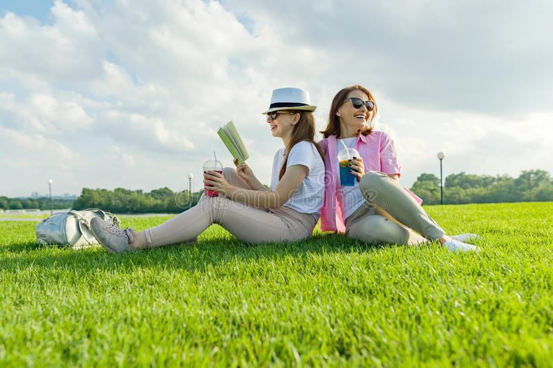 Communication of parent and teenager. Mother and teen daughter sitting on green lawn in the park and reading book, drinking cool c. Ocktail and enjoying summer stock photo