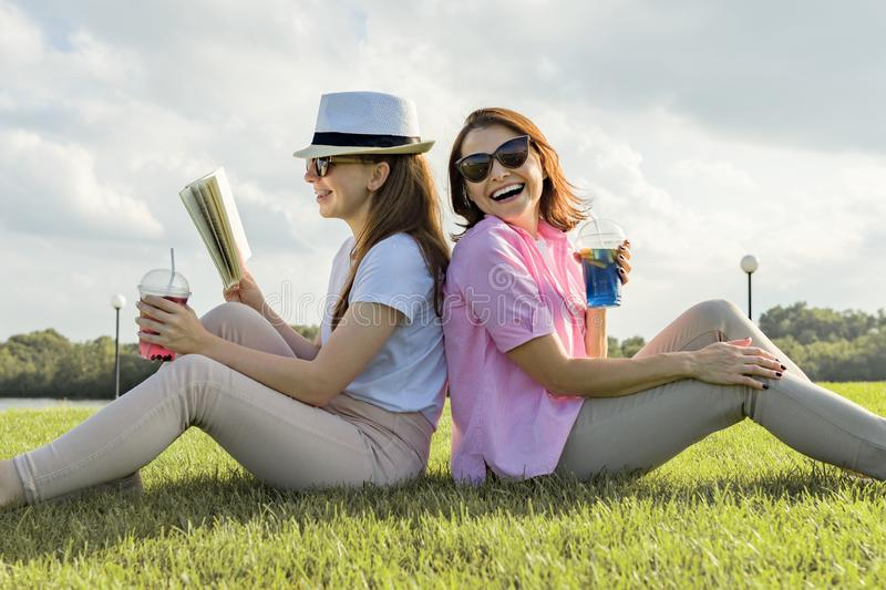 Communication of parent and teenager. Mother and teen daughter sitting on green lawn in the park and reading book, drinking cool c. Communication of parent and royalty free stock images