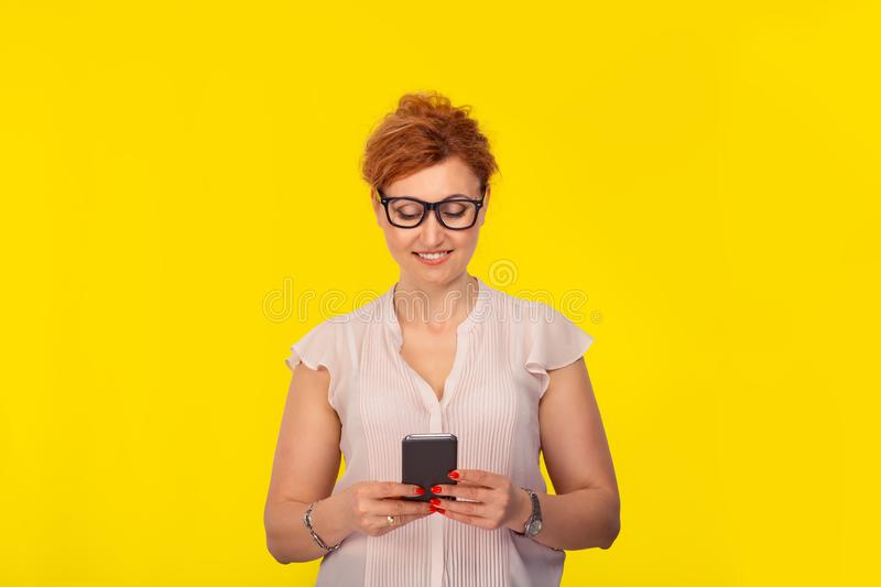 Woman holding looking at smartphone texting smiling royalty free stock photos