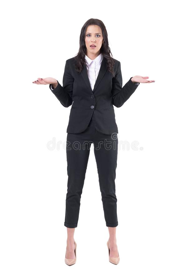Communication problems concept. Shocked confused young business woman shrugging shoulders. royalty free stock image