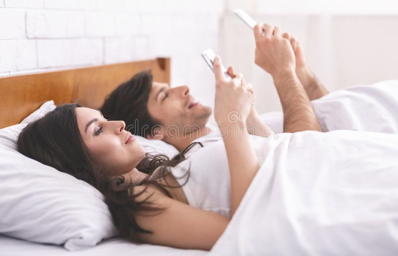 Young couple using cellphones in bed, ignoring each other stock photos