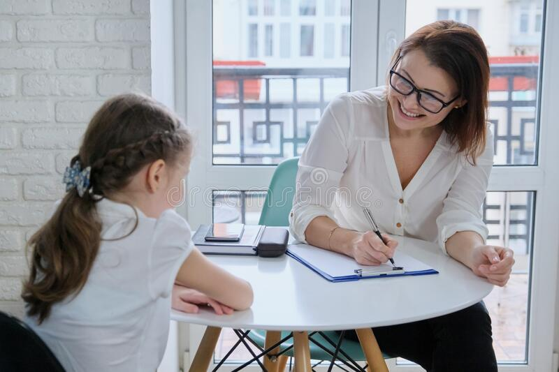 Communication session of school psychologist and girl child royalty free stock photography