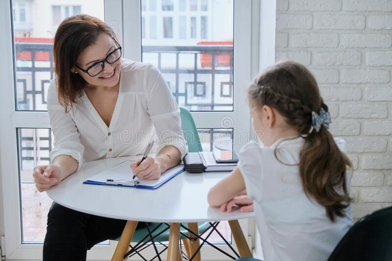Communication session of school psychologist and girl child stock photos