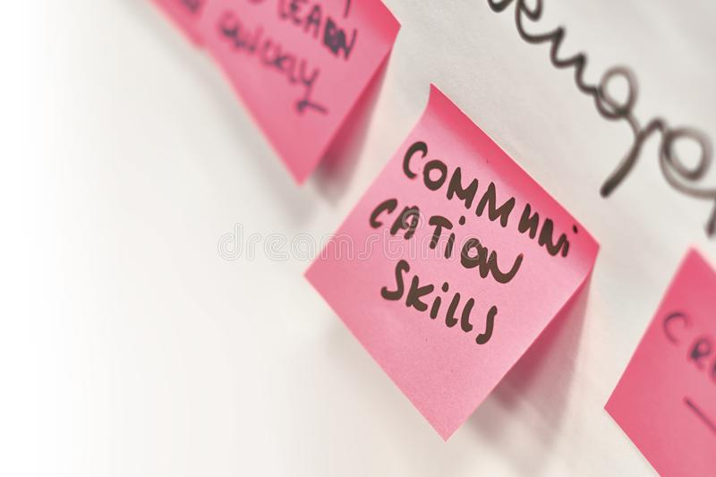 Communication skills written on pink paper stickers attached to a flip chart royalty free stock photo