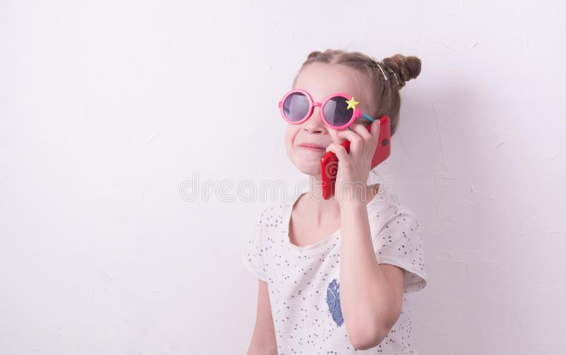 Communication technologies: A girl in pink glasses emotionally talks on the red phone. Portrait at the white wall stock photo