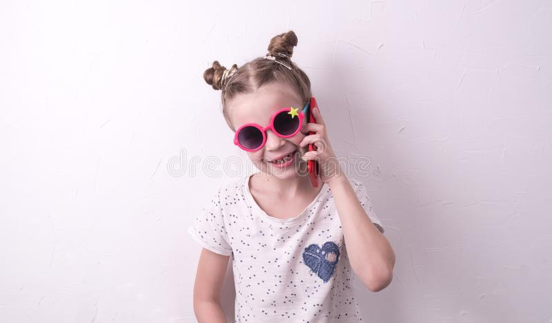Communication technologies: A girl in pink glasses emotionally talks on the red phone. Portrait at the white wall royalty free stock photos