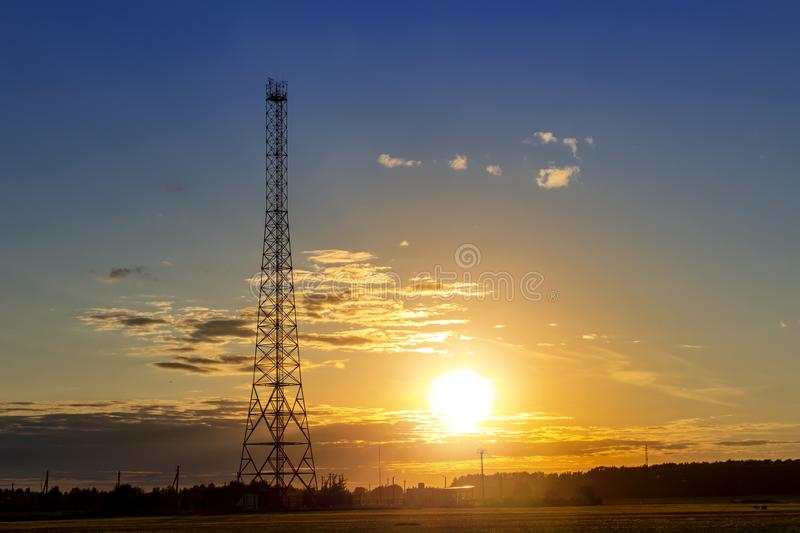 Communication tower against summer sunset background. Cell, network, phone, telecommunication, technology, transmission, wave, aerial, data, digital, evening stock images