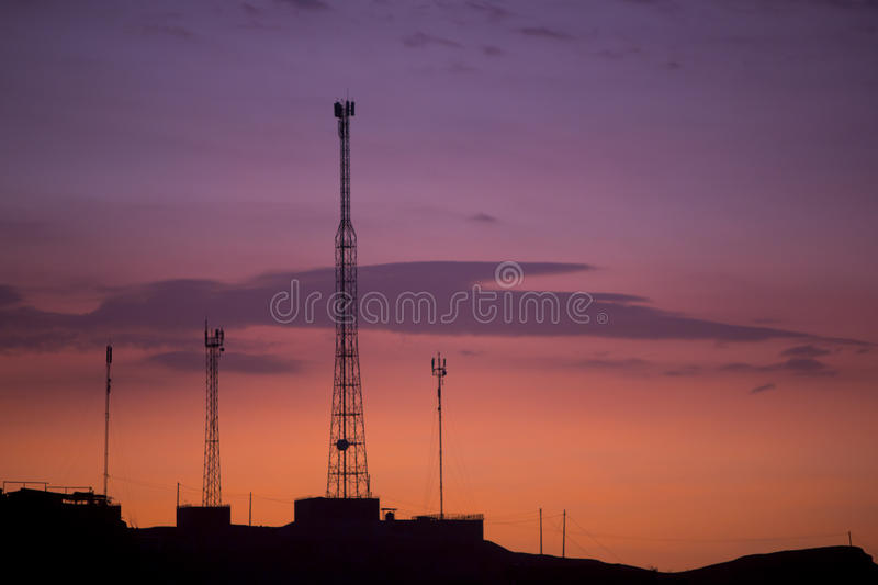 Communication towers on orange purple sky background, Peru. Orange purple sunset with silhouette of telecommunication towers and phone cables in Mancora. Peru royalty free stock photo