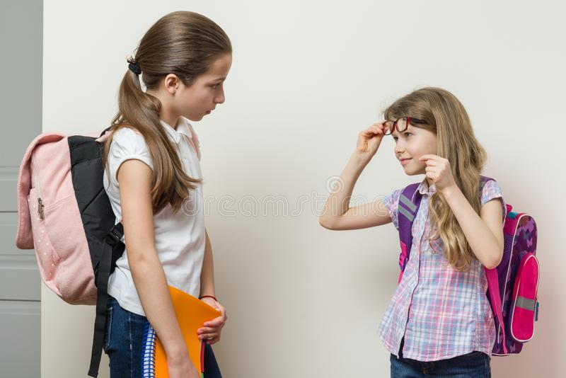 Communication of two girls at school. Schoolgirls with backpacks, background bright wall at school stock photos