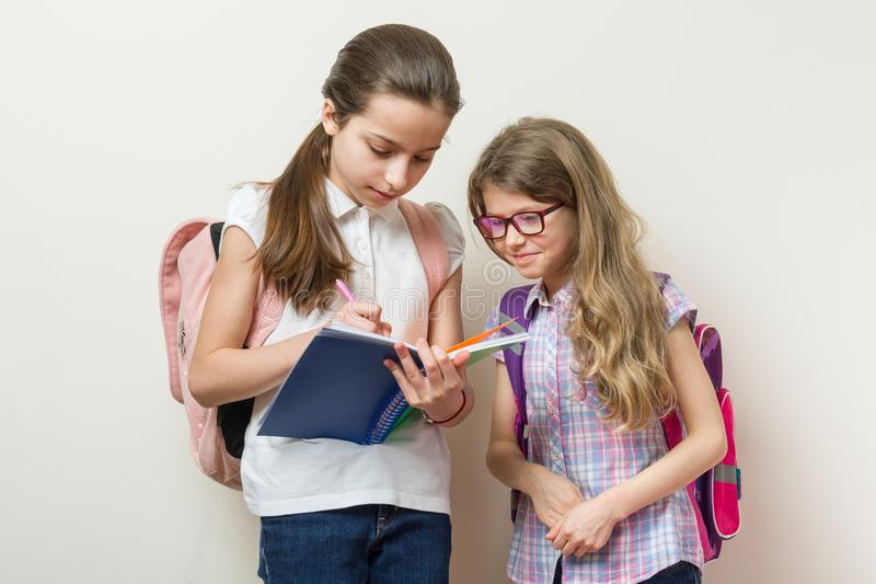 Communication of two girls at school. Schoolgirls with backpacks, books, background bright wall at school. Communication of two girls at school. Schoolgirls royalty free stock image