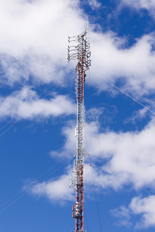 Communications antenna lattice truss tower. Metal lattice truss tower with telecommunication antennas against clouds and blue sky stock photography