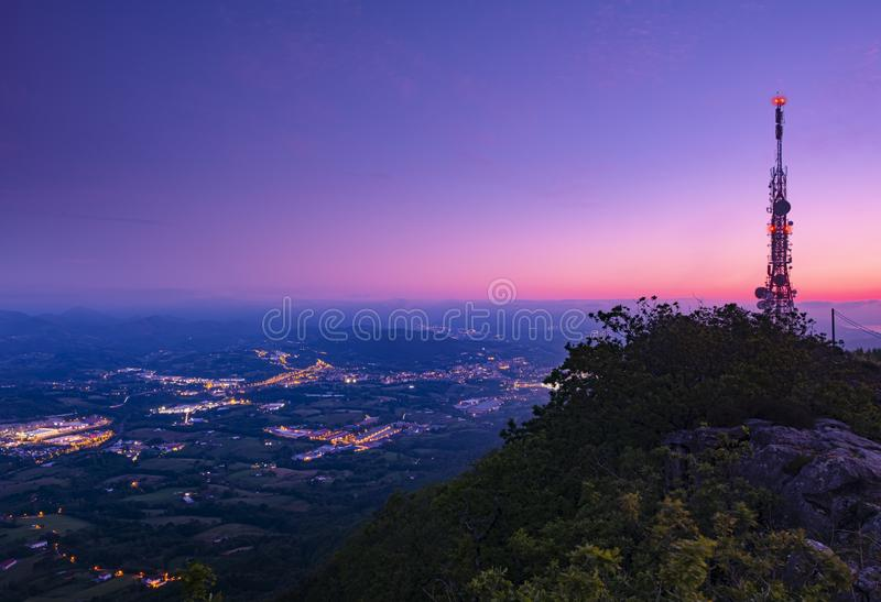 Communications tower over the city providing information and internet to mobiles, Sunset at the Jaizkibel mountain royalty free stock photography