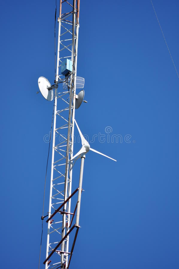 Communications Tower. View from below of a Communications Tower with satellite dishes, ISP and a wind turbine royalty free stock photo