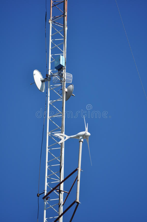 Communications Tower. View from below of a Communications Tower with satellite dishes, ISP and a wind turbine stock image