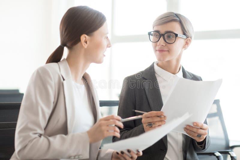 Communicerende in vrouwen met documenten stock afbeelding