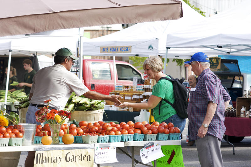 Community Farmers' Market. More consumers are supporting farmers' markets these days in response to a trend to buying fresh local produce. A tomato grower makes royalty free stock photos