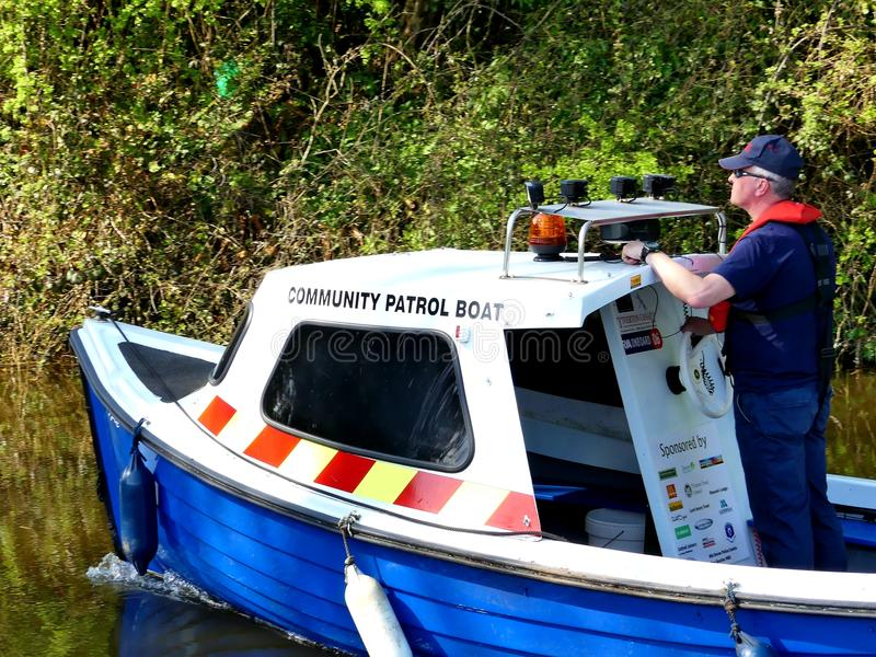 Community patrol boat drives up the Great Western canal, Sampford peverell, Devon, England royalty free stock photo