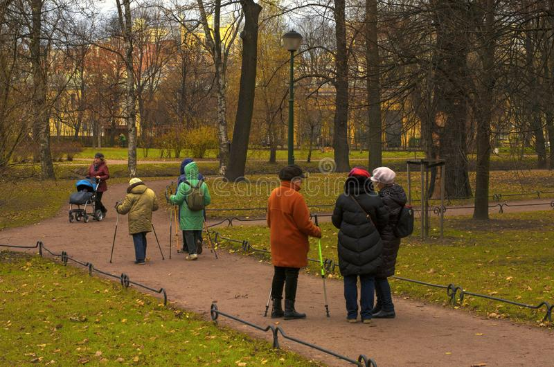 Community of seniors engaged in Nordic walking in the Park. Saint Petersburg, Russia - November 16, 2018: Community of seniors engaged in Nordic walking in the royalty free stock photos