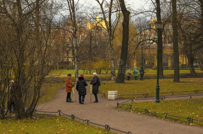Community of seniors engaged in Nordic walking in the Park. Saint Petersburg, Russia - November 16, 2018: Community of seniors engaged in Nordic walking in the royalty free stock images