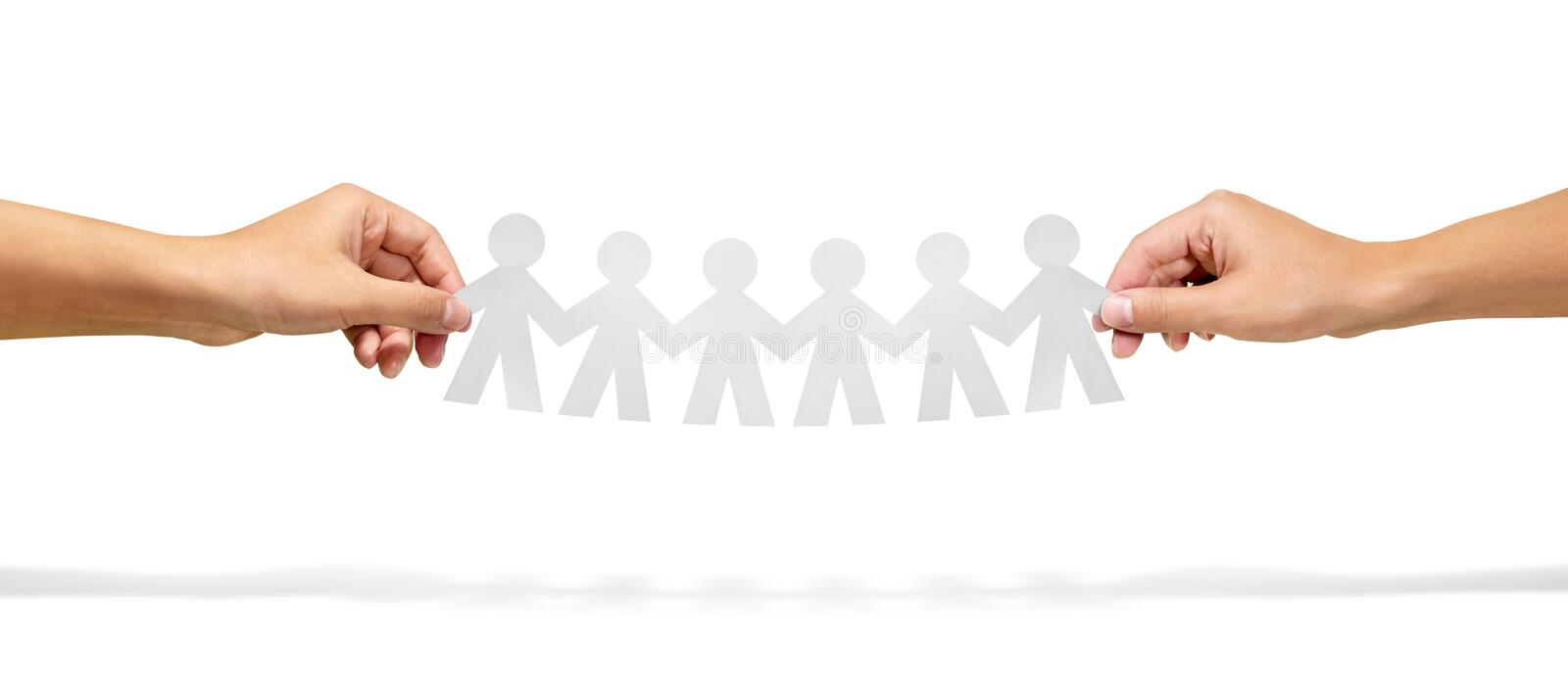 Community, unity and teamwork concept - hands holding paper chain people over white background stock photos