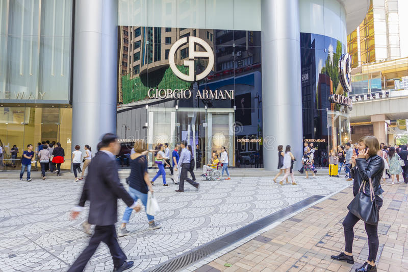Communters eller shoppare som går passerandet som Giorgio Armani lagrar arkivbilder