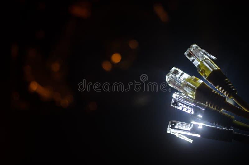 Commutateur de réseau et câbles d'Ethernet, symbole des télécommunications mondiales Le réseau coloré câble sur le fond foncé ave photographie stock