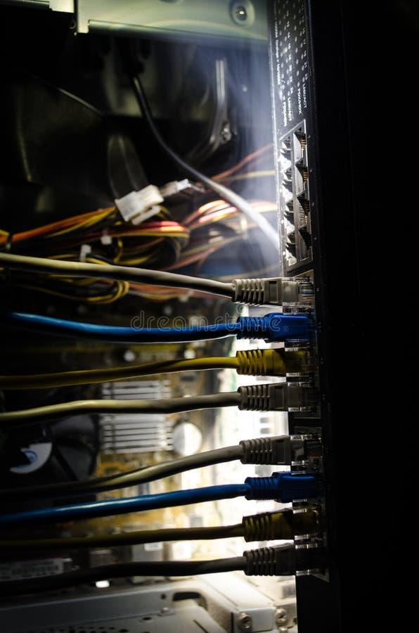 Commutateur de réseau et câbles d'Ethernet, symbole des télécommunications mondiales Le réseau coloré câble sur le fond foncé ave photographie stock libre de droits