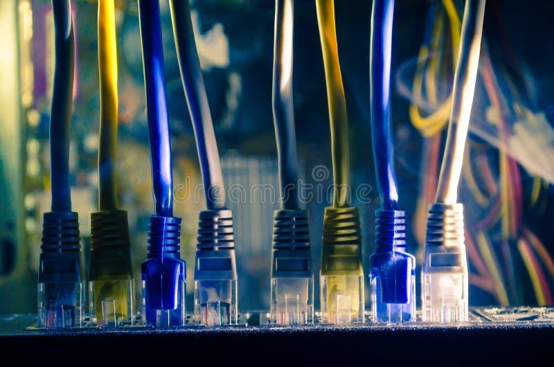 Commutatore di rete e cavi di Ethernet, simbolo delle comunicazioni globali La rete colorata cabla su fondo scuro con le luci e l immagine stock