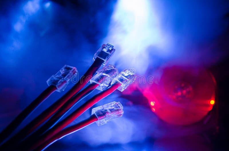 Commutatore di rete e cavi di Ethernet, simbolo delle comunicazioni globali La rete colorata cabla su fondo scuro con le luci e l fotografia stock libera da diritti