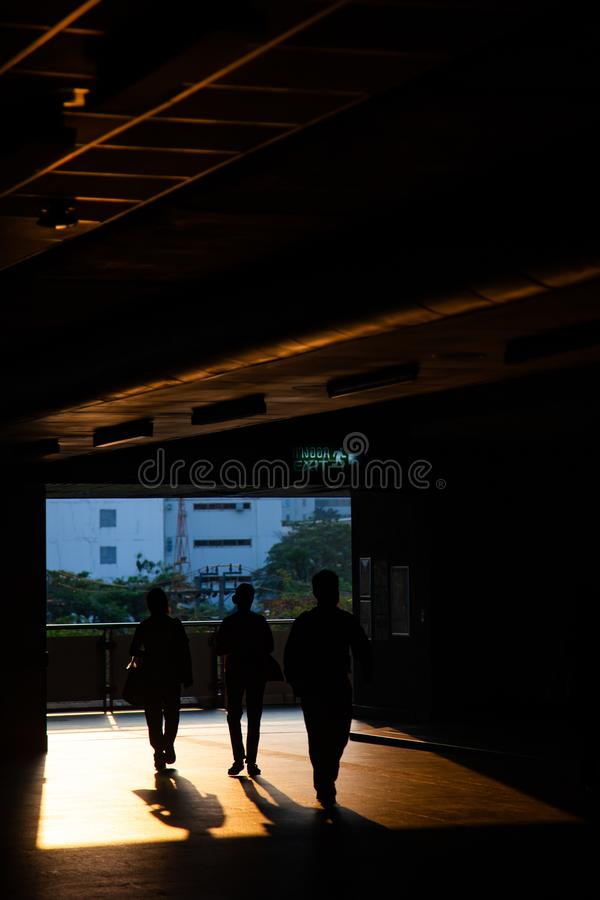 Commuter silhouettes in a station in early morning. Railway, architecture, railroad, transportation, travel, train, people, sky, passenger, urban, reflection royalty free stock image