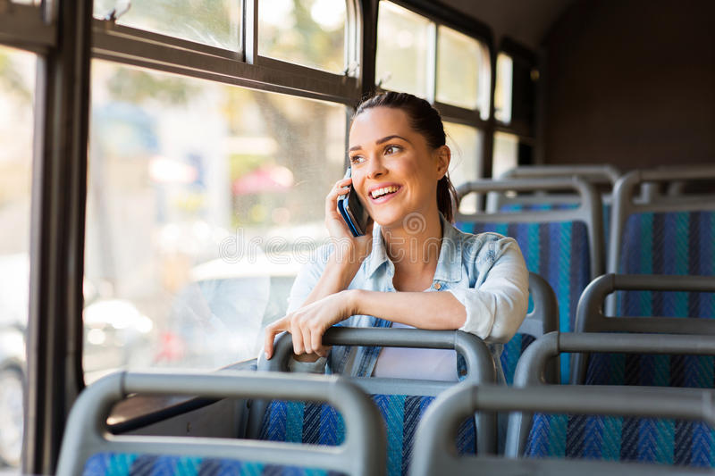 Commuter talking cell. Beautiful female commuter talking on cell phone while taking bus to work stock images