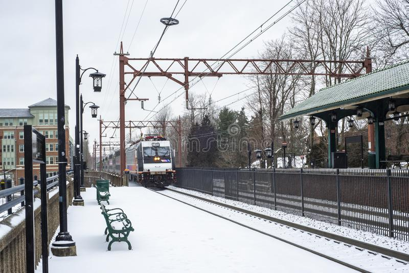 commuter train arriving at train station after snow. stock images
