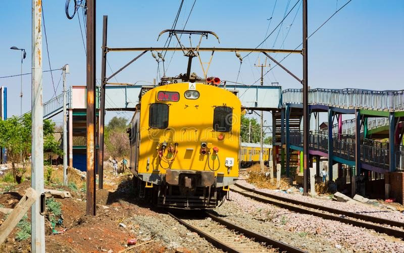 Commuter Train moving through the heart of Soweto, Johannesburg. Soweto, South Africa - September 08 2018: Commuter Train moving through the heart of Soweto royalty free stock image