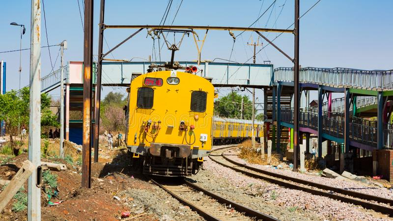 Commuter Train moving through the heart of Soweto, Johannesburg. Soweto, South Africa - September 08 2018: Commuter Train moving through the heart of Soweto royalty free stock photography