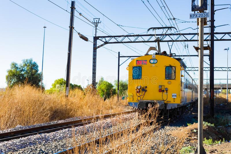 Commuter Train moving through the heart of Soweto, Johannesburg. Soweto, South Africa - September 08 2018: Commuter Train moving through the heart of Soweto royalty free stock photo