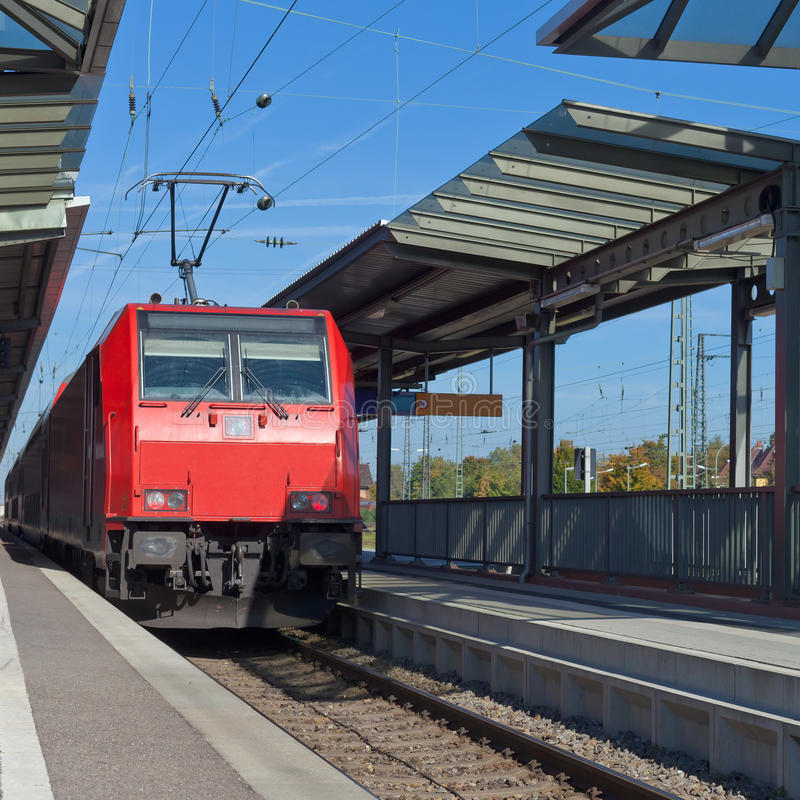 Commuter train at station. Commuter train with red electric locomotive engine is about to leave railway station royalty free stock photos