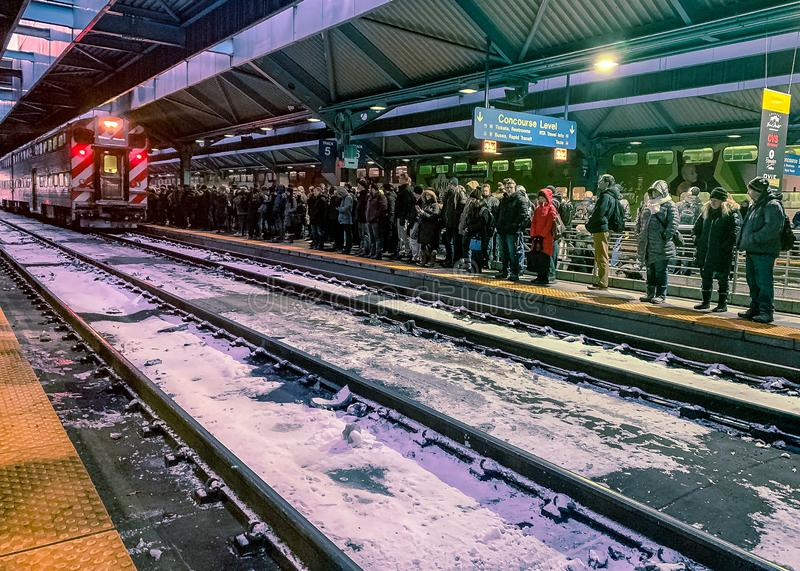 Commuters lined up on train platform in Ogilvie Train Station, watching delayed Metra train arrive royalty free stock photo