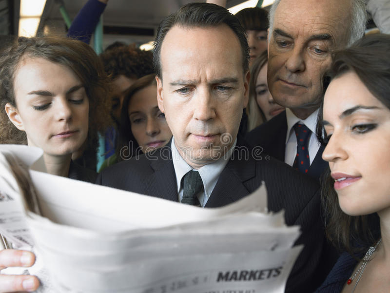 Commuters Reading Newspaper In Train. Closeup of a group of commuters reading newspaper in train stock image