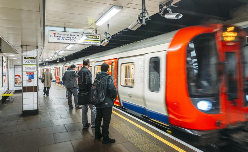 Commuters at Tower Hill Station on the London Underground with a fast-approaching train on the platform royalty free stock image