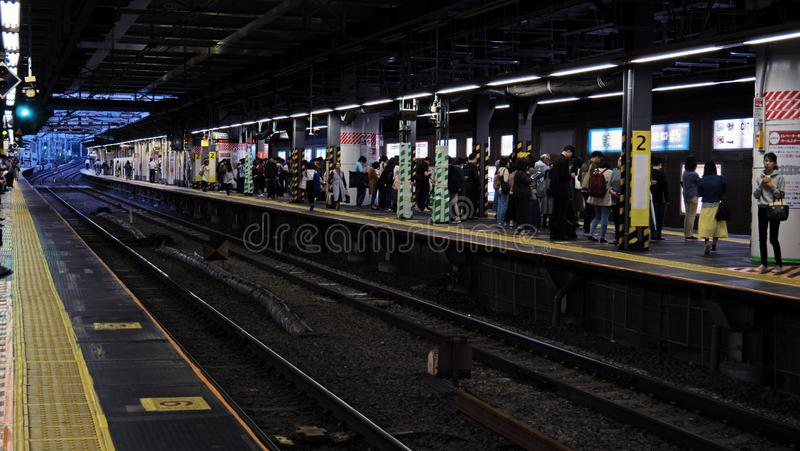 Commuters wait on a busy subway station platform at an underground station in Tokyo Japan. The dusk evening light and bright lights of the neon signs light the stock photography