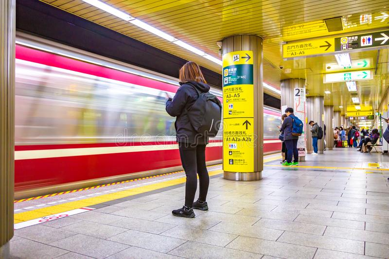 Commuters wait for the train to stop to get on at one of the subway stations in Tokyo, Japan stock image
