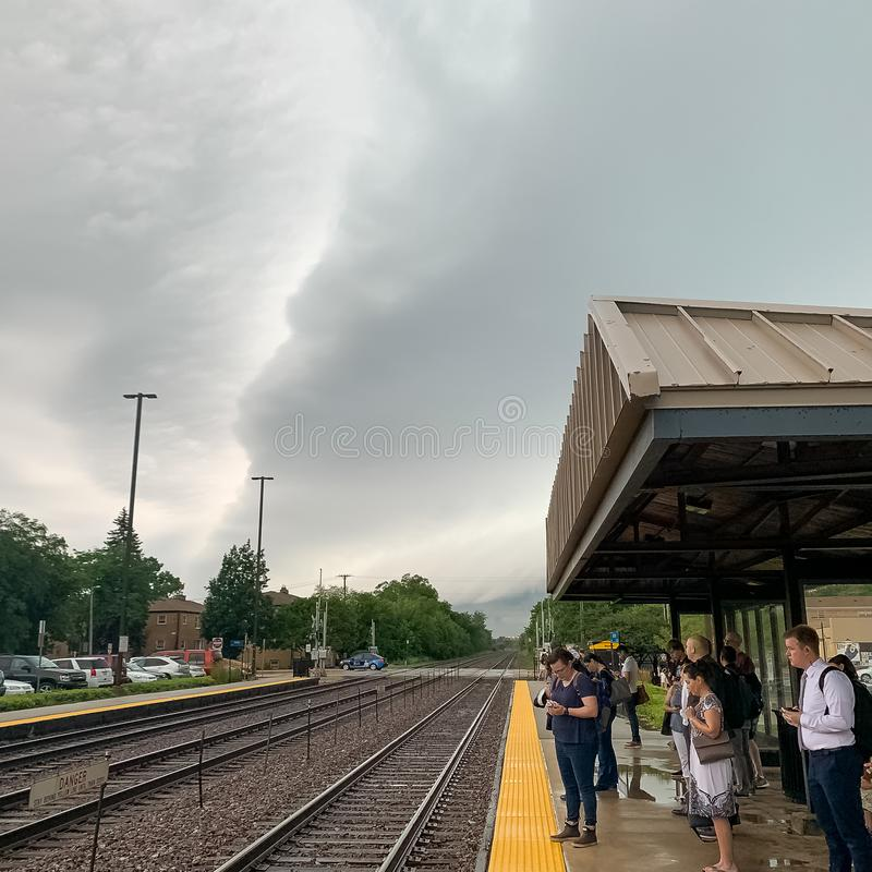 Commuters wait at the Villa Park, IL metra trian station while a heavy storm system begins to arrive stock photos