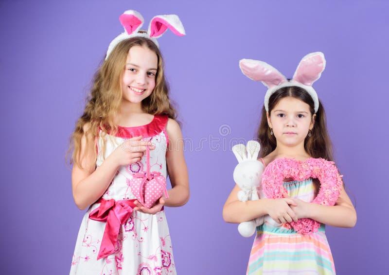 Como conejos de conejito Niños lindos en el estilo del conejito de pascua que lleva a cabo corazones Pequeños niños en vendas del imágenes de archivo libres de regalías