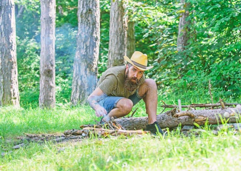 Como construir fora a fogueira Arranje os galhos das madeiras ou as varas de madeira que estão como uma pirâmide e coloque as fol foto de stock