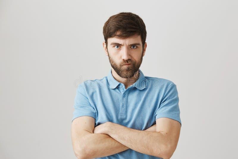 Como devo eu o punir para tal comportamento Retrato do indivíduo maduro irritado incomodado com a barba que está com mãos cruzada imagens de stock